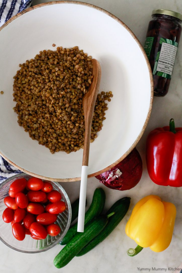 Mediterranean lentil salad ingredients on a white countertop include cooked green lentils, tomatoes, cucumber, bell peppers, and olives.