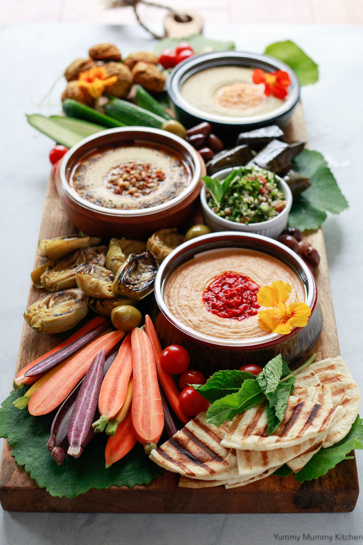 A mezze appetizer platter with hummus, rainbow carrots, flatbread, artichokes, and falafel is perfect as a vegetarian or vegan party platter.