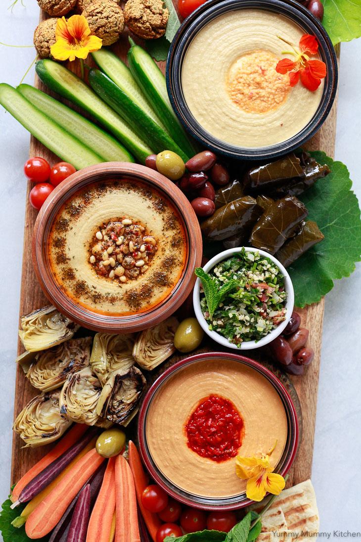 A beautiful hummus platter with bowls of hummus, tabbouleh, vegetables, and falafel makes a great Mediterranean Greek appetizer that's vegetarian and vegan.