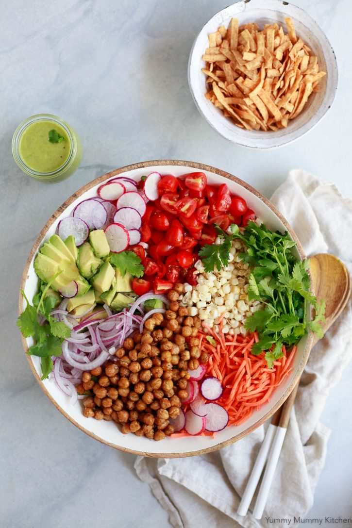 A beautiful Southwestern style salad with sections of roasted chickpeas, radish, corn, tomatoes, red onion, and cilantro. A jar of avocado dressing and bowl of tortilla crisps on the side. This Southwest salad is naturally vegetarian, vegan, and gluten-free.