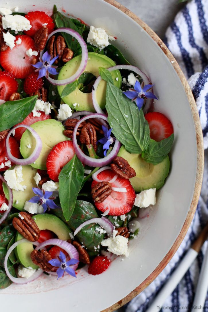 A close-up photo of a beautiful strawberry spinach salad with basil, avocado, pecans, and feta.