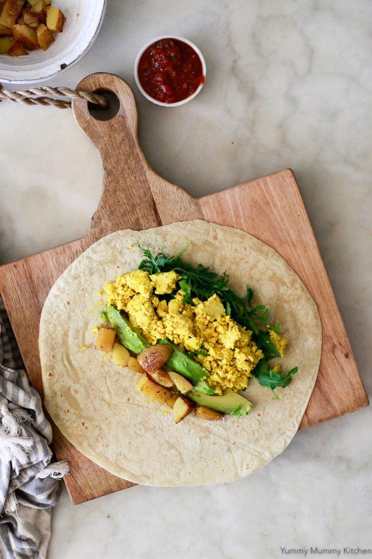 Tofu scramble, arugula, avocado, and potatoes go into a tortilla for this vegan breakfast burrito recipe.
