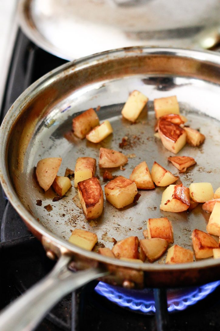 Baby yellow potatoes roast in a frying pan on the stove before going into a vegan breakfast burrito.