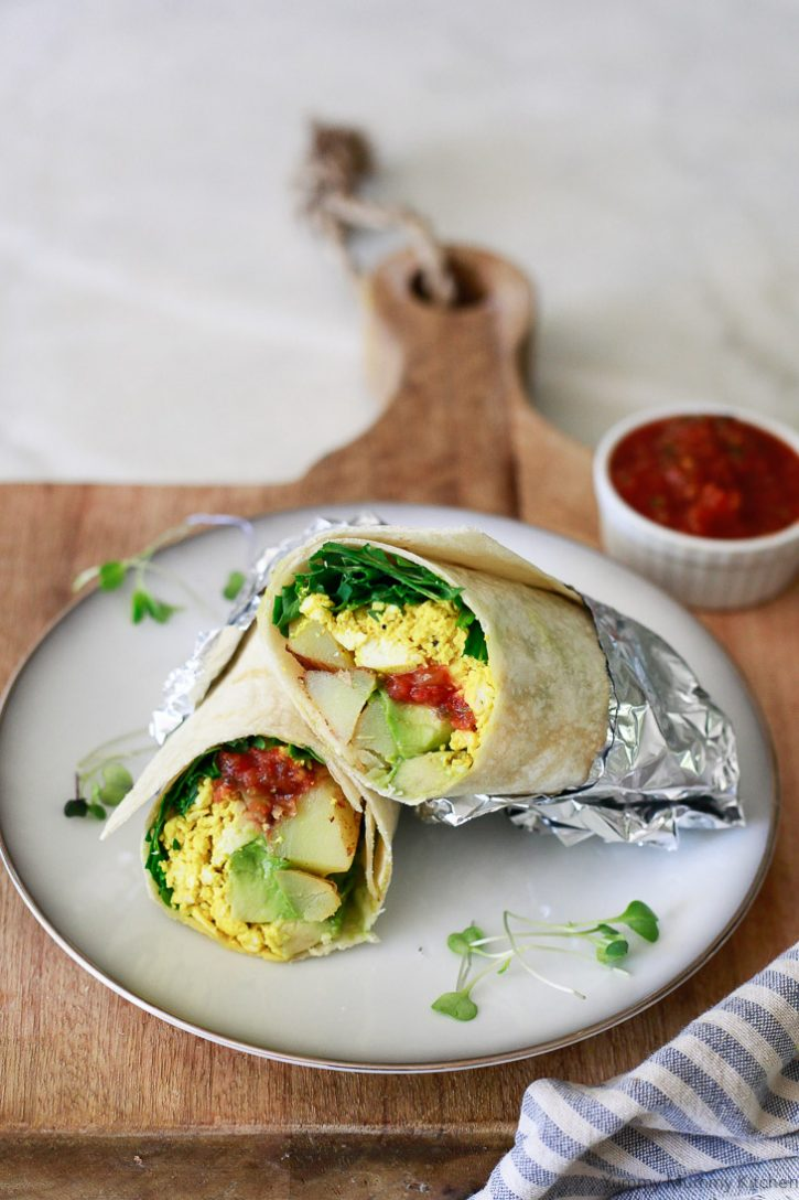 A vegan breakfast burrito filled with tofu scramble, potatoes, salsa, avocado, and greens cut in half on a plate.