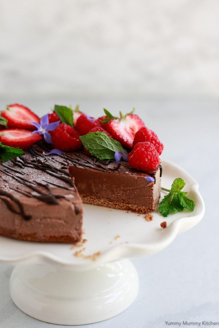 A beautiful vegan chocolate cheesecake topped with berries sits on a cake stand.