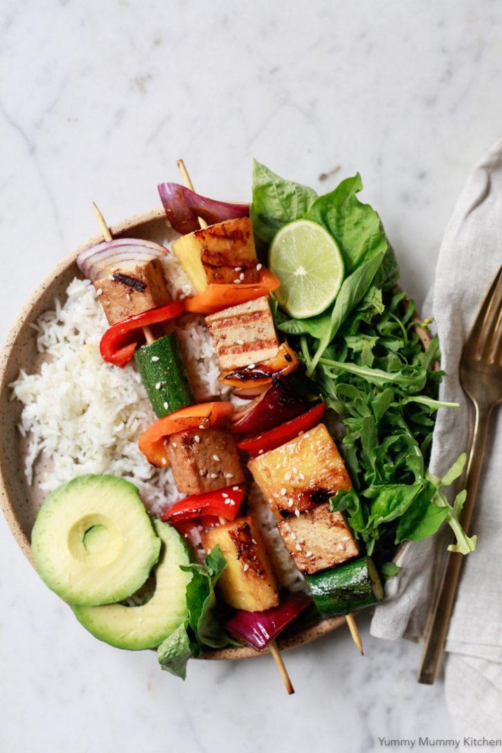 Grilled vegetable, pineapple, and tofu shish kabobs served with rice, salad, and avocado. This grilled veggie kabob recipe is so easy and perfect for a vegetarian or vegan BBQ.