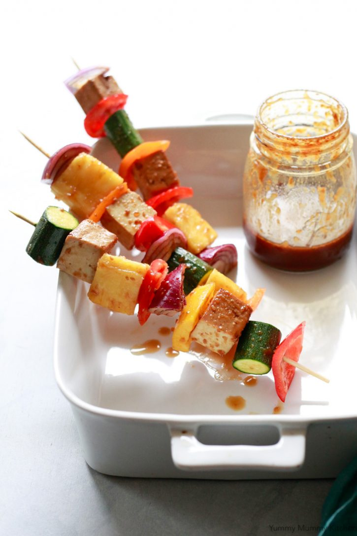 Vegetable, tofu, and pineapple on wooden skewers are coated in homemade teriyaki sauce and ready for the grill. Grilled veggie shish kabobs are the best summer vegetarian BBQ recipe