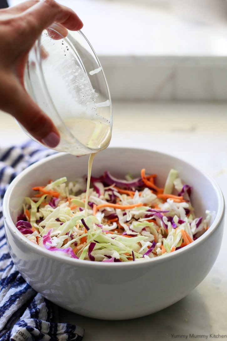 Vegan coleslaw dressing gets poured over a bowl of cabbage and carrot slaw.