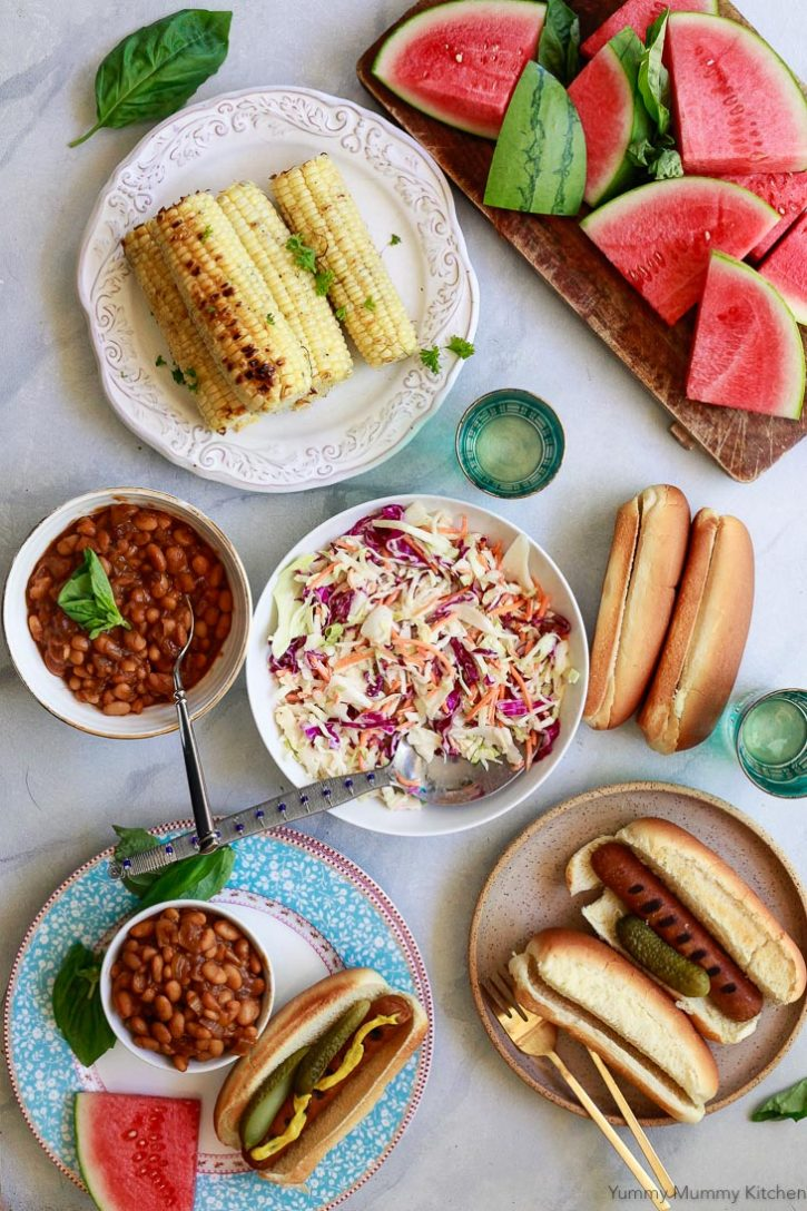 Beautiful photo of a vegetarian summer BBQ with veggie dogs, vegetarian baked beans, vegan coleslaw, watermelon and corn.