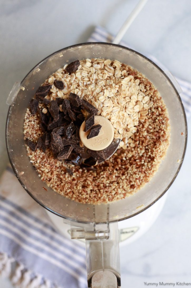 Oats and dark chocolate are added to a food processor to make healthy no-bake oatmeal cookie bites.
