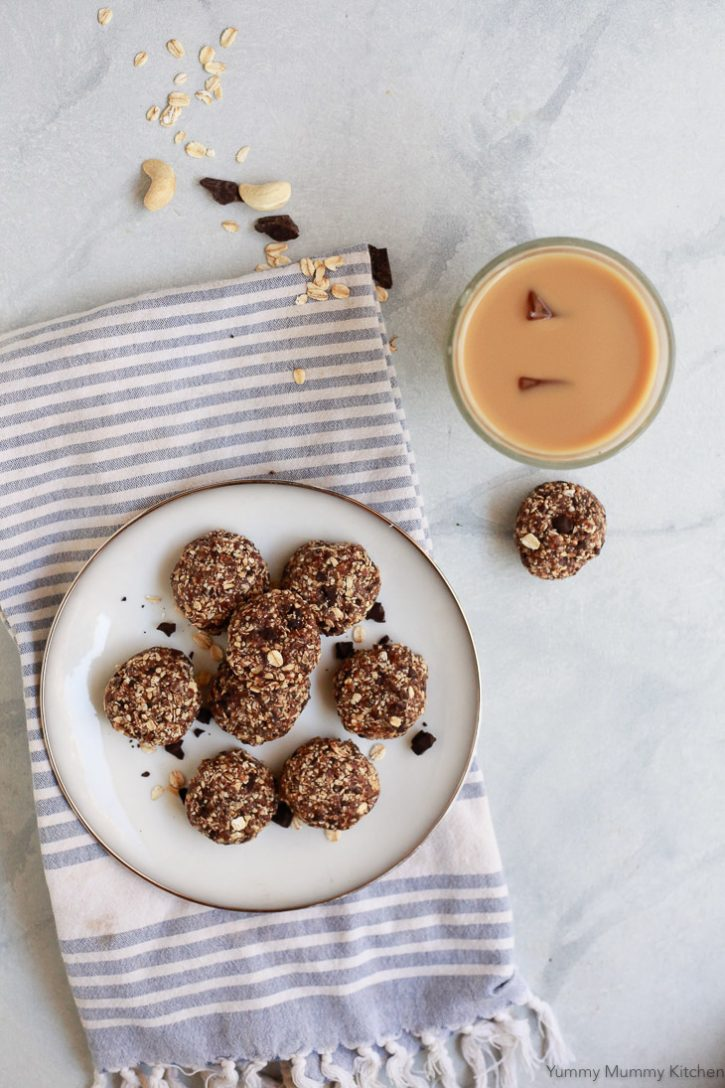 A plate of healthy no-bake oatmeal cookies on a white plate with a cup of iced coffee.