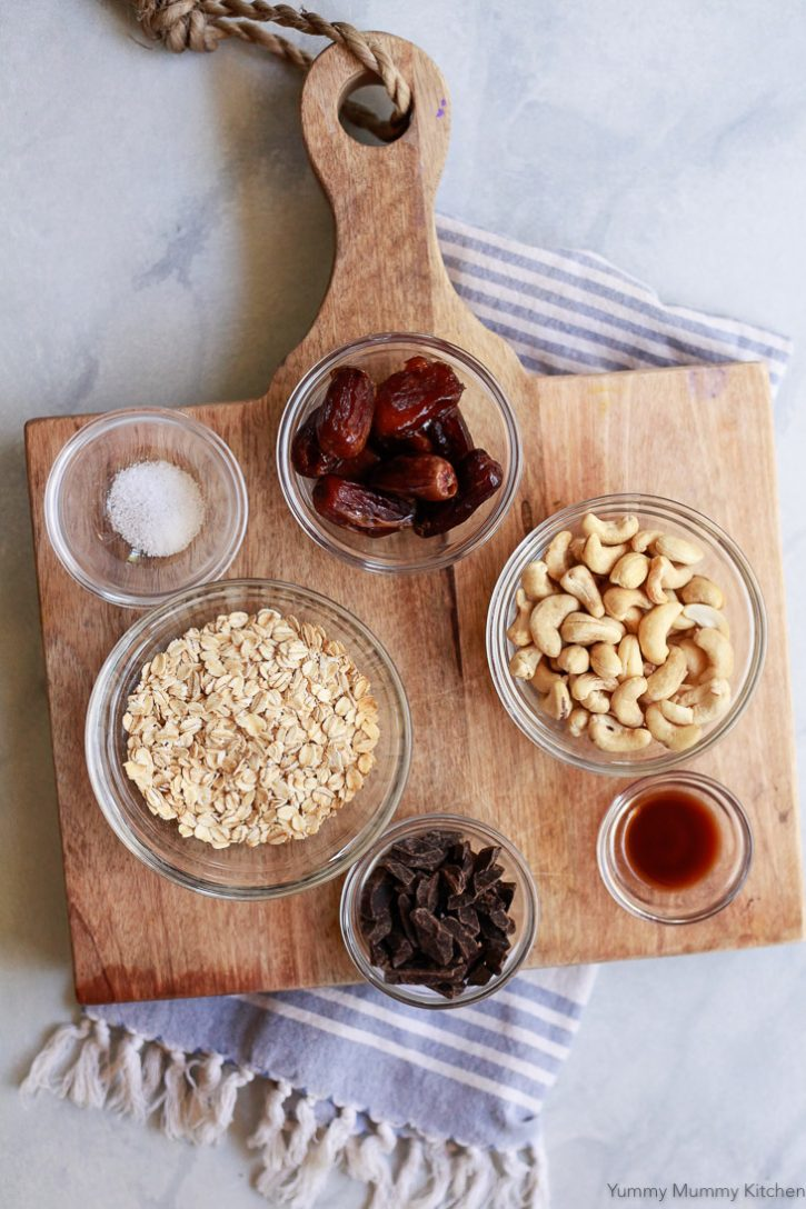 Ingredients for healthy no-bake oatmeal cookies include oats, dates, cashews, maple syrup, and dark chocolate.