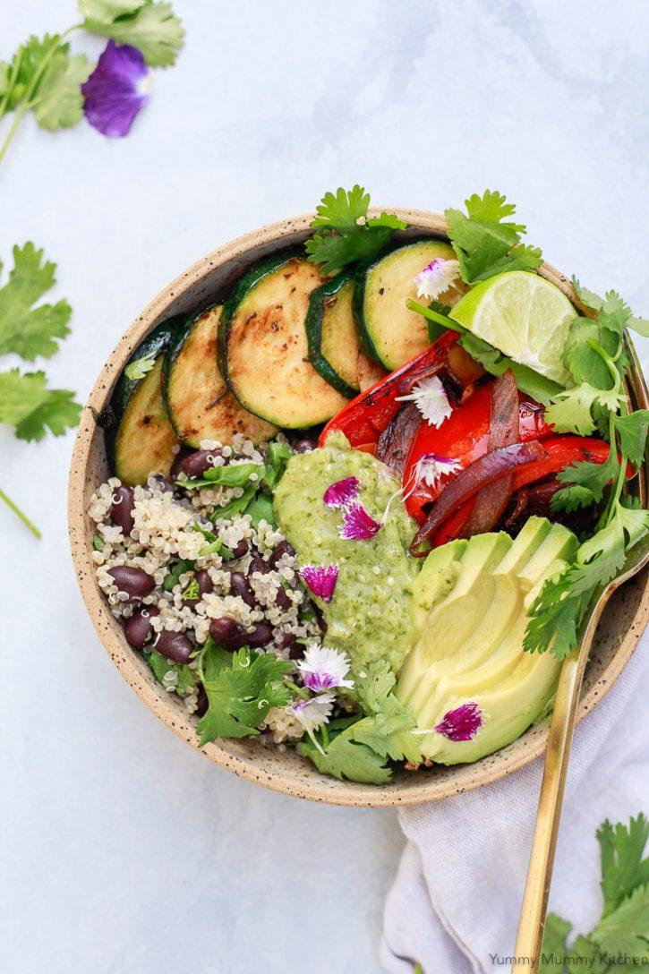 A beautiful vegan burrito bowl with quinoa, black beans, vegetables, avocado, and homemade roasted tomatillo salsa verde.