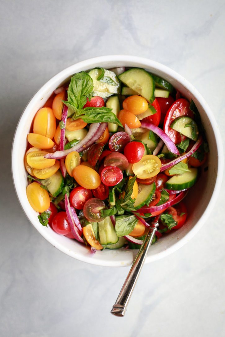 A bowl of marinated tomato, cucumber, onion, basil salad with balsamic dressing.