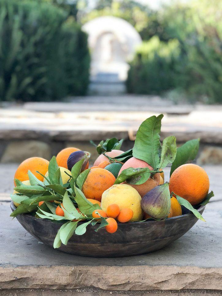A beautiful wooden bowl filled with backyard citrus fruits like lemons, oranges, kumquats, and grapefruit.