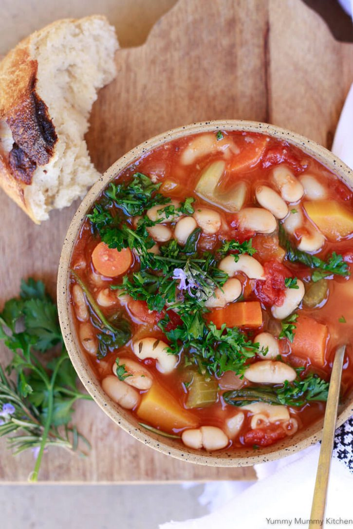 A bowl of Instant Pot Minestrone soup made with vegetables, beans, and pasta topped with fresh herbs and served with crusty bread.