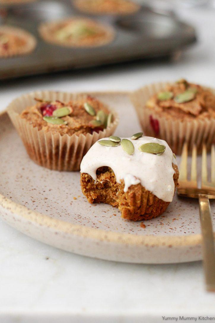 Beautiful vegan gluten free pumpkin muffins with cinnamon cream cheese frosting and pepitas.
