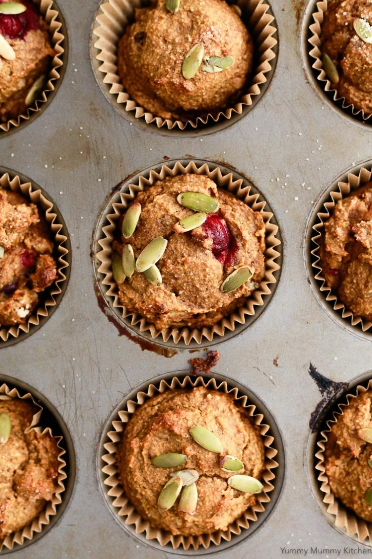 Pumpkin muffins in a tin with fresh cranberries and pepitas. These deliciously healthy pumpkin muffins are vegan and gluten free.