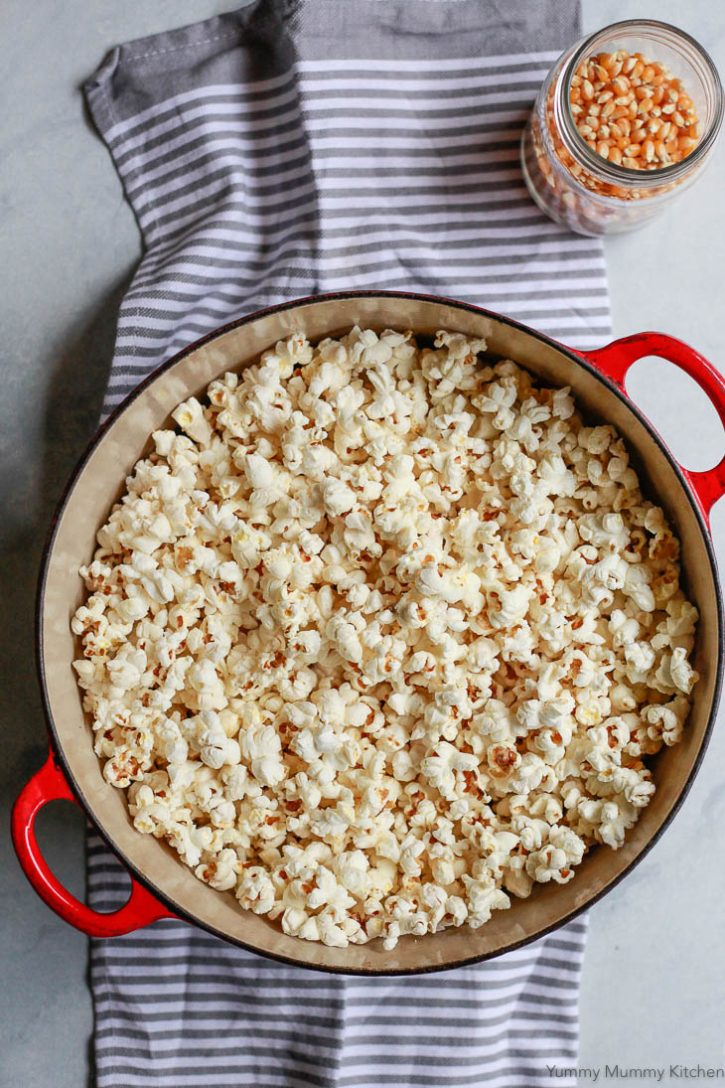 A Dutch oven filled with fresh homemade stovetop popcorn. Find out how to make popcorn on the stove with this easy recipe.