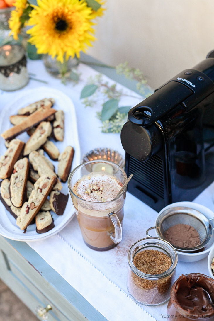 Nepresso machine on a table with homemade biscotti and flowers for a beautiful coffee bar.