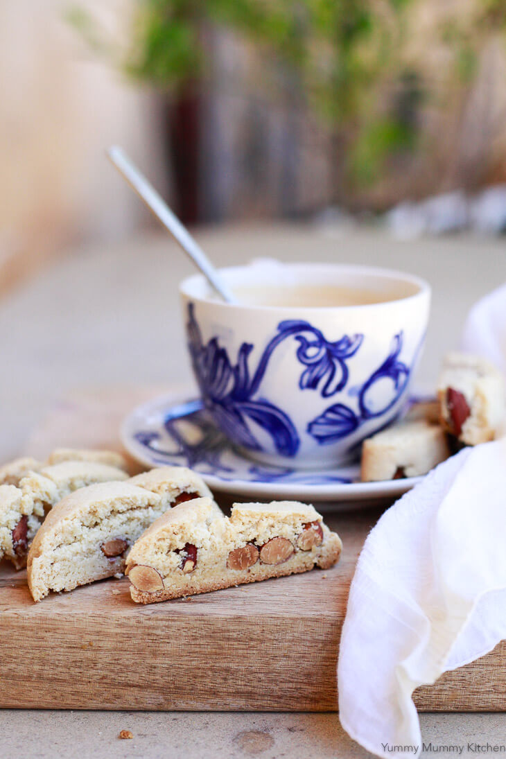 Slices of almond biscotti sit on a cutting board outside with a blue and white tea cup in the background.