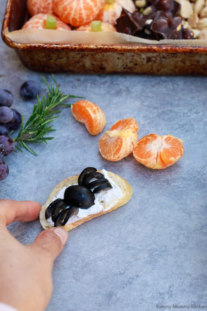 A cute Halloween spider made out of an olive on top of crostini and cheese. What a cute and delicious Halloween party appetizer finger food idea.