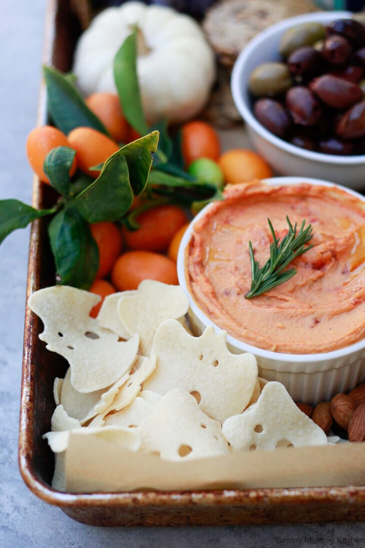 Boo chips on a Halloween party platter with red pepper hummus, olives, fruit, cheese, and nuts.