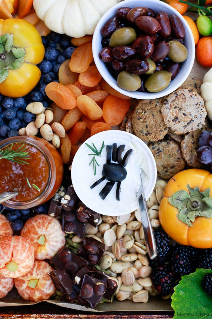 Halloween party finger food appetizer board with olives, spiders, tangerine pumpkins, fruit and cheese.