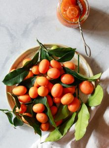 A bowl of freshly picked kumquats sits on a white countertop.