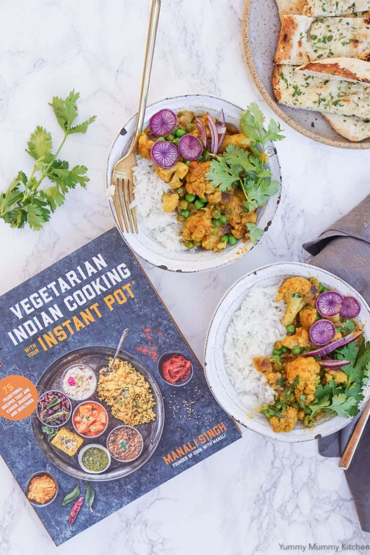 Bowls of Gobi Matar Korma (Cauliflower and Pea Coconut Curry) with rice, cilantro, and purple radish on a counter with the Vegetarian Indian Cooking with your Instant Pot cookbook.