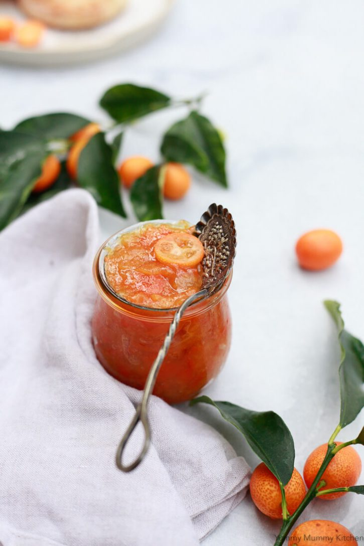 Beautiful orange kumquat marmalade in a Weck jar with a jam spoon and fresh kumquats.