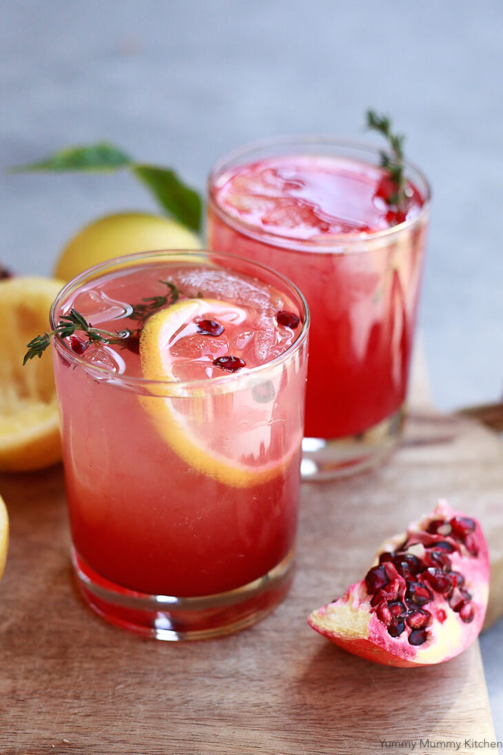Apple cider vinegar drinks with lemon and pomegranate juice on a cutting board.