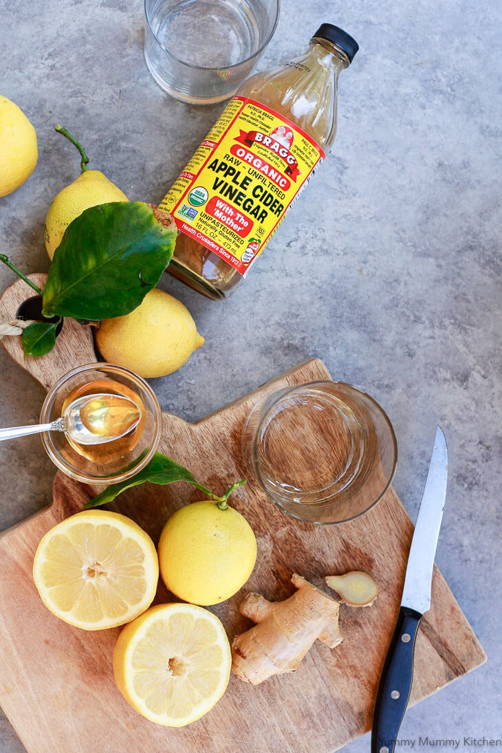 Ingredients for an apple cider vinegar drink recipe including lemons, Bragg ACV, ginger, and honey on a cutting board.