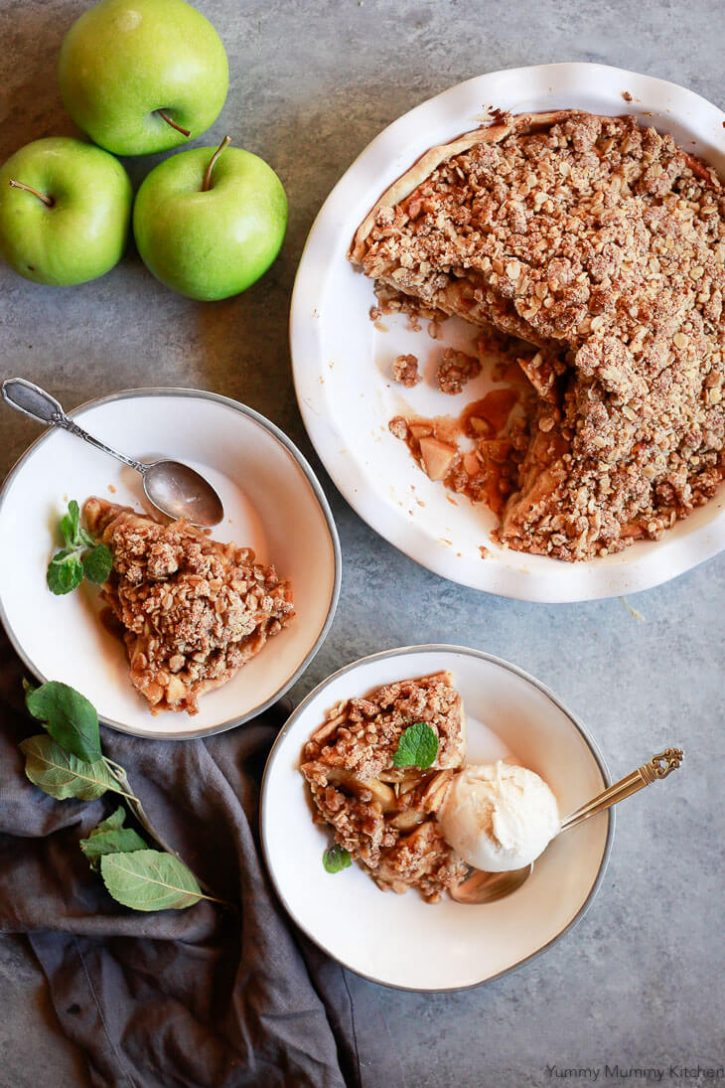 Apple crumble pie is served with vegan ice cream. This beautiful vegan apple pie has a crumb topping made with oats, coconut sugar, and almond flour. It's gluten-free and delicious for Thanksgiving or Christmas.