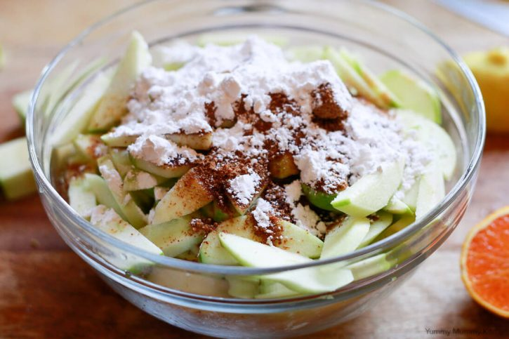Coconut sugar, spices, and arrowroot are added to sliced apples to make apple crumble pie filling.