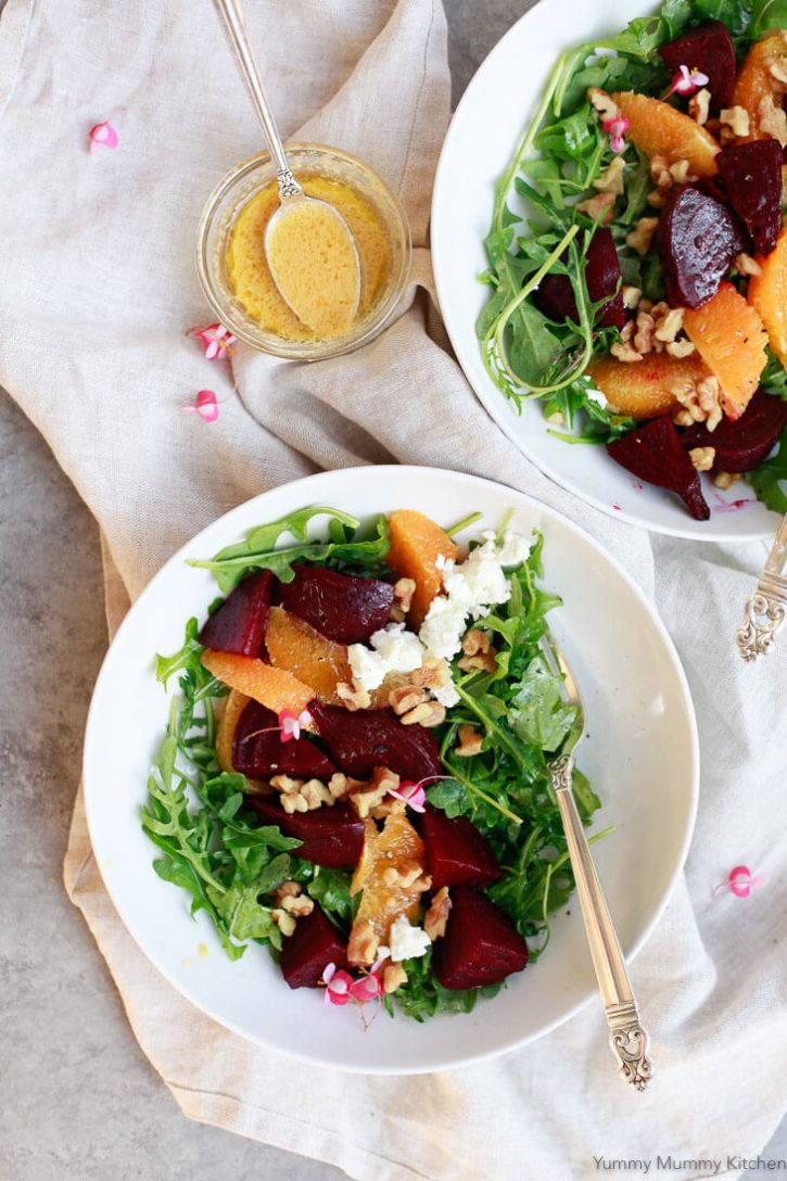 Bowls of beautiful beet salad over arugula with orange segments. The perfect winter salad.
