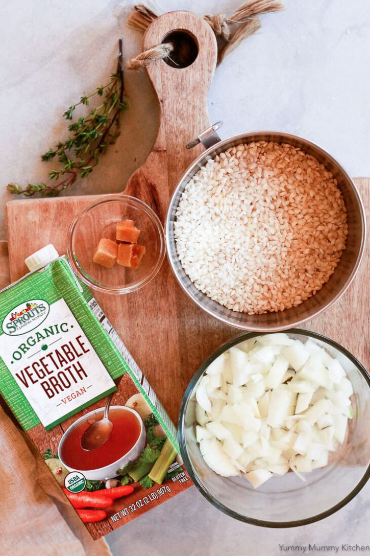 Instant Pot risotto ingredients include arborio rice, chopped yellow onion, garlic, and vegetable broth.