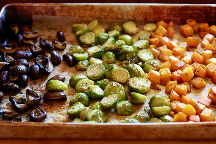 A sheet pan of roasted vegetables: mushrooms, Brussels sprouts, and butternut squash are ready to top Instant pot vegetable risotto.