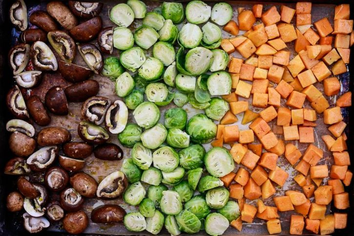 Raw mushrooms, Brussels sprouts, and butternut squash cubes drizzled with olive oil sit on a sheet pan before roasting for vegetable risotto.