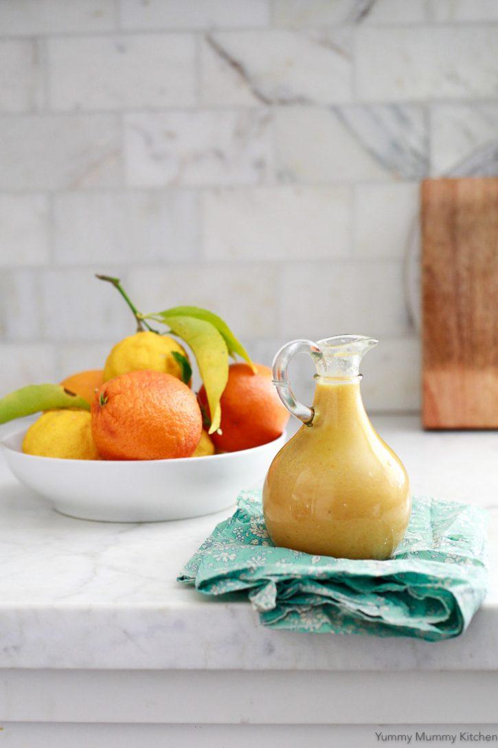 A jar of orange vinaigrette sits on a counter for beet salad.