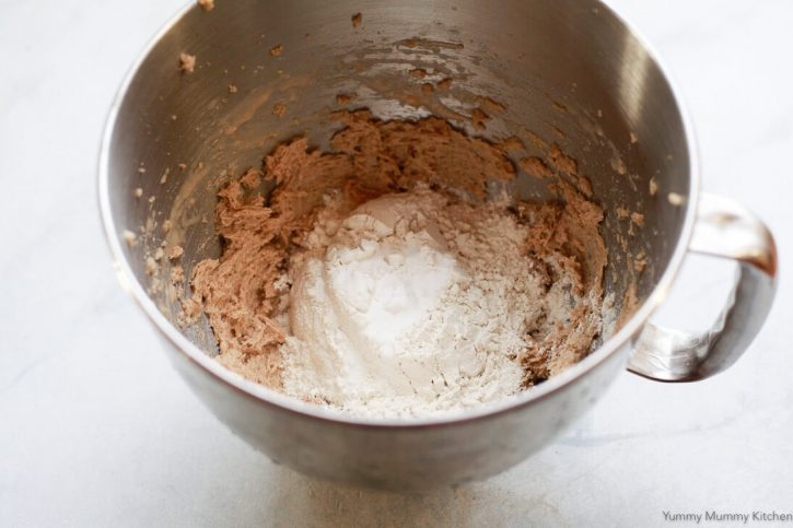 Flour and baking soda are added to creamed butter, sugar, and egg for vegan chocolate chip cookies.