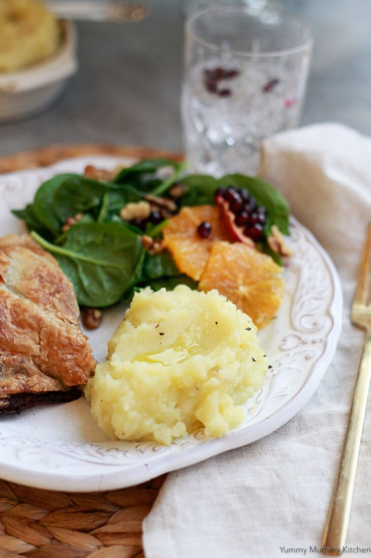 A vegan Thanksgiving or Christmas dinner plate with vegan mashed potatoes, Wellington, and salad.