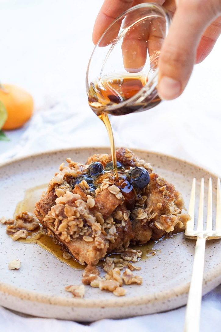 A plate with vegan gluten free french toast casserole with an oat crumble topping. Topped with fresh blueberries, maple syrup is poured over this vegan breakfast treat.