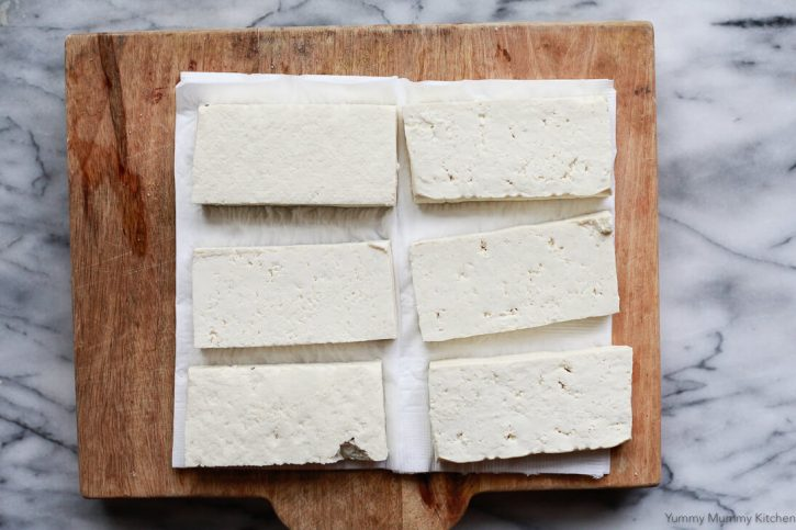 A block of tofu is cut into slabs and pressed on paper towels.
