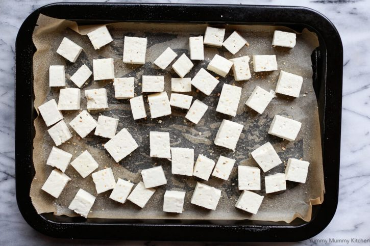 Cubed extra firm tofu on a parchment lined baking sheet before going into the oven. How to bake tofu.