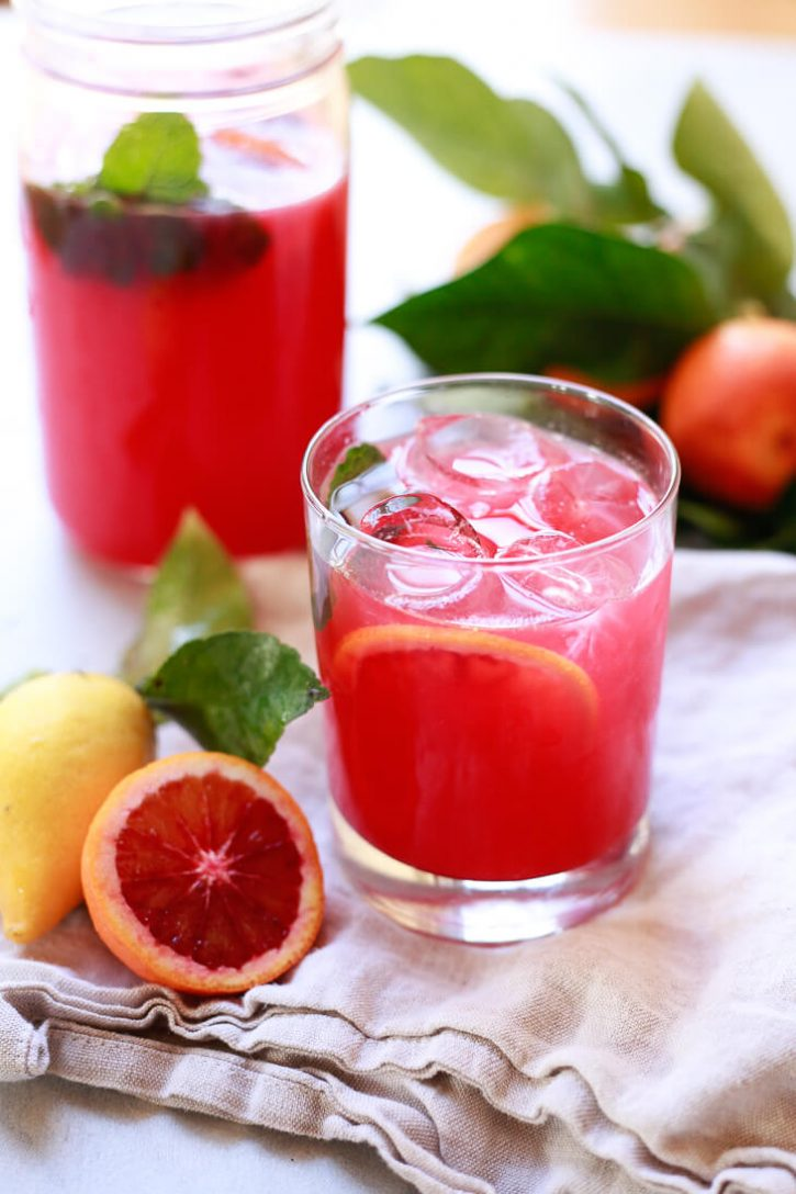 A glass of beautiful pink blood orange lemonade with a slice of blood orange and sprig of mint.