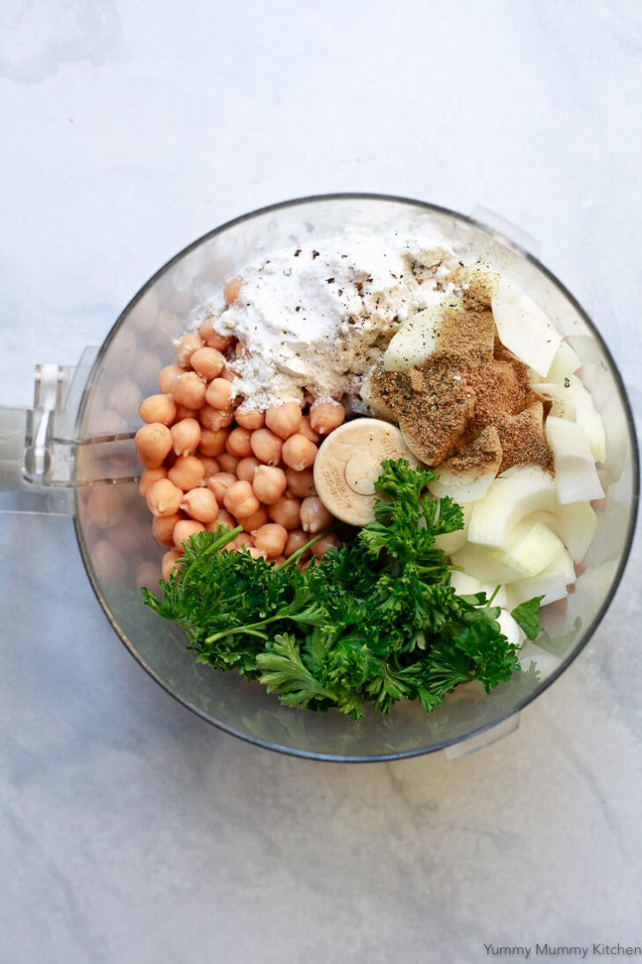 Canned chickpeas, fresh parsley, onion, spices, and flour in the bowl of a food processor ready to make falafel.