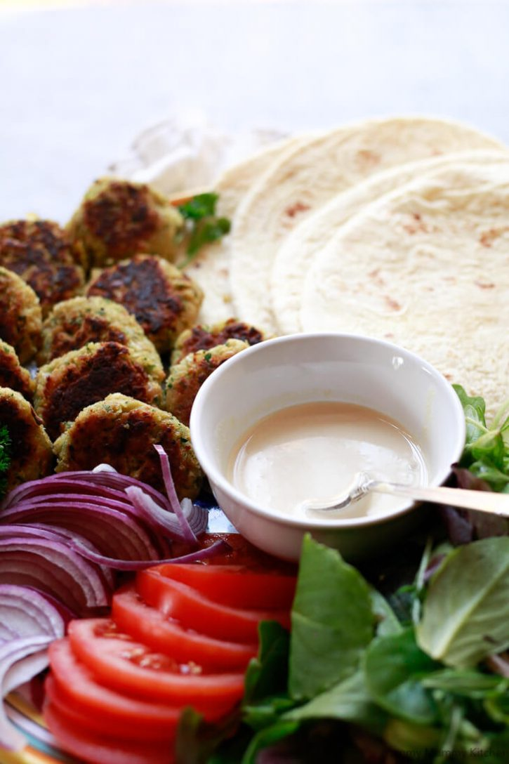 A close-up photo of a bowl of homemade tahini sauce in the middle of a DIY falafel wrap platter.