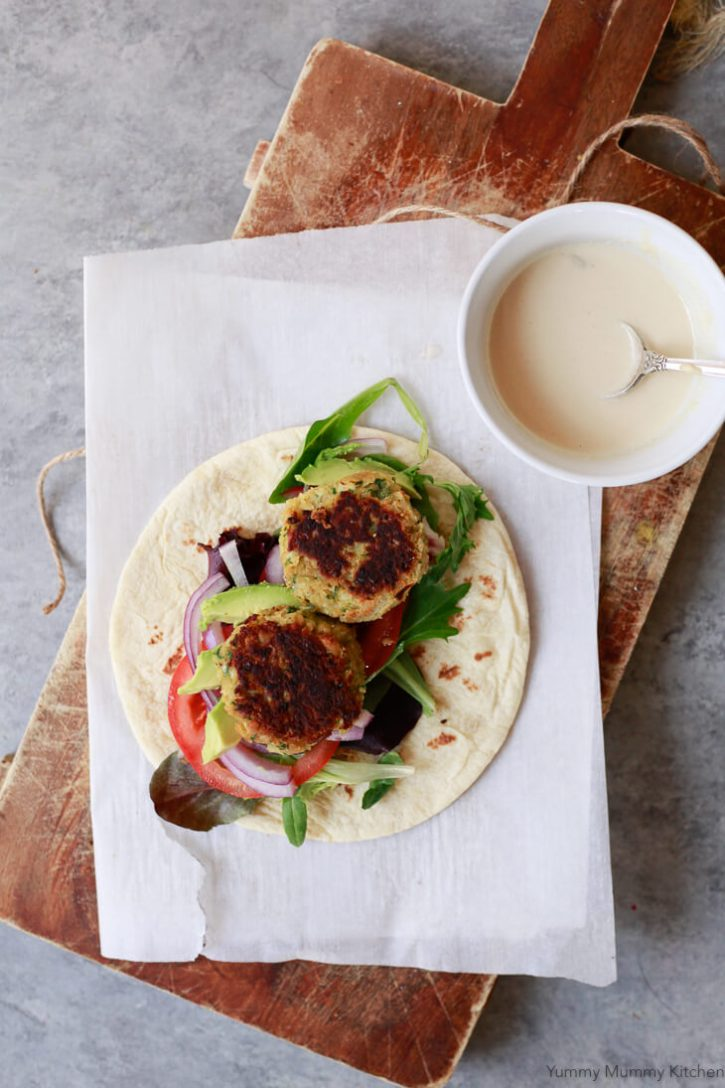 An open falafel wrap on flatbread with vegetables and tahini sauce sits on a cutting board with parchment.