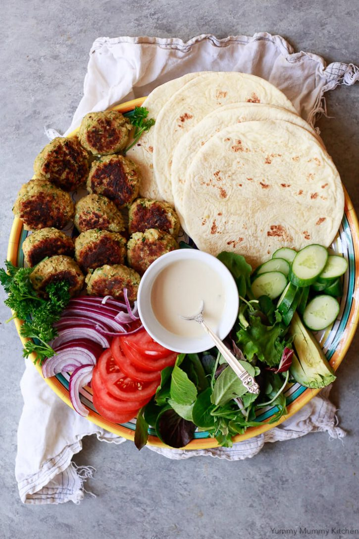 A platter topped with baked falafel, cucumbers, tomatoes, lettuce, onions, tahini sauce, and flatbread for a healthy vegan dinner.